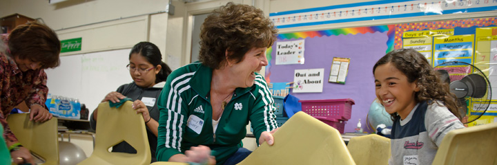 Dolly Duffy, executive director of the Notre Dame Alumni Association, shares a light moment with a child at a recent service project.